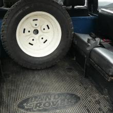 The rear of the V8 land rover 90 has got 2 bench seats at the sides and the spare wheel is in the middle behind the front seats