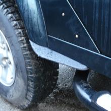 A picture showing the rear wheel of a 110 land rover fitted with dirt defenders to stop mud splashing up the sides