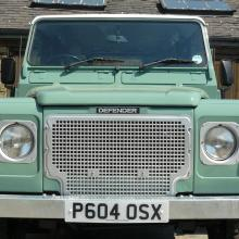 A Light green 110 land rover showing a silver heritage grille
