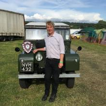 107 LAND ROVER AT MASHAM STEAM RALLY WITH TROPHY FOR THE BEST RESTORED LAND ROVER WITH JOHN WRIGHT STOOD NEXT TO IT .
