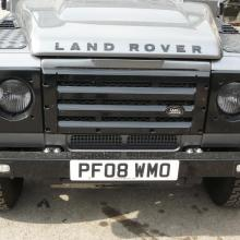 A silver land rover defender fitted with an XS radiator grille