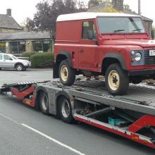 A vehicle transporter is outside Jake wright specialists in land rover's  after collecting the land rover  ready for transportation to Southampton docks and then onto a ship bound for Washington in USA