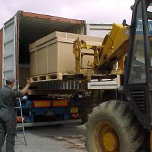 A container is being loaded at jake wright's with a large box containing land rover spare parts