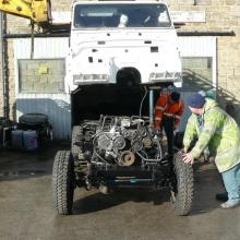 A Mechanic is watching as the land rover defender 110 body is being lowered onto the chassis