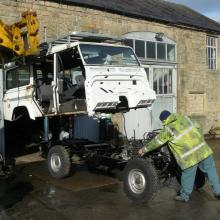 The Tele-Handler is lowering the land rover defender body onto the new chassis