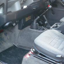 The left hand  side of the front inside the land rover showing the seats