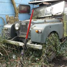 land rover station wagon series one 107 seen here abandoned in a garden where it lay without rear axle for 20 years and can be seen covered in ivey