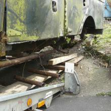 land rover series 1 107 being removed from the garden using rollers made out of old boiler tube under the rear springs as the axle had previously been removed .