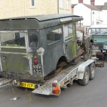 land rover series 1 being winched onto the trailer using a land rover defender.