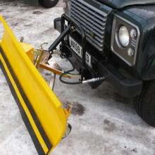 A Land rover Defender is seen standing on a snowy surface with a snow plough fitted