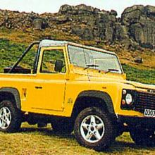A nice yellow land rover defender with open top on Ilkley moors in West Yorkshire with the Cow and calf rocks in the background