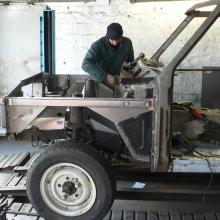 range rover body shell being prepared in the workshop with a mechanic