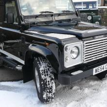 A very nice looking black defender land rover 90 with silver grilles and headlamp surrounds