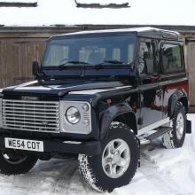 A nice picture of the land rover which is for sale seen outside the showroom with snow on the ground