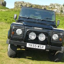 "The front of the land rover defender is fitted with an ""a"" bar and spotlights"