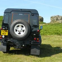 The rear end view of The land rover defender on Ilkley moors near the cow and calf rocks