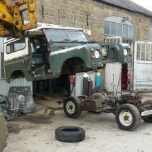 The land rover series 2a body is now being removed using a forklift