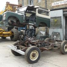 The land rover body is being carefully removed using a forklift
