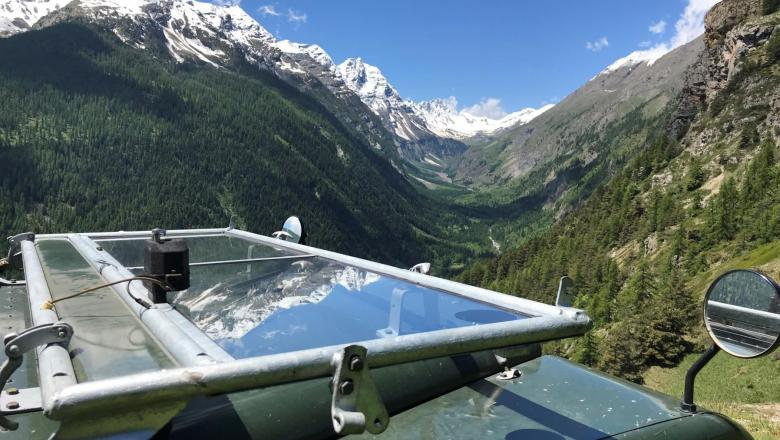 Here is a beutiful picture showing a 1951 land rover with it's windscreen folded down onto the bonnet standing at 2,200 feet above sea level today in the Alps. I the background the snow capped mountains can be seen with a lovely green valley below .