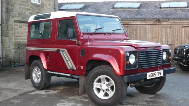 Land rover defender county in red with 7 seats