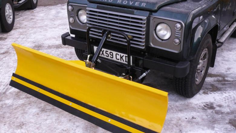 HERE IS A SNOW PLOUGH ON THE FRONT OF A LAND ROVER DEFENDER