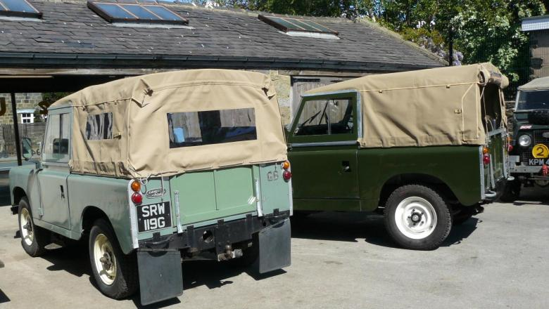 Land Rover Series with soft tops are seen in the yard at Jake Wright's