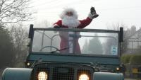 Father christmas is standing in a series one land rover waving top passers by