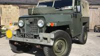 A very nice land rover series 2a is standing in the yard at jake wright land rover outside the showroom .